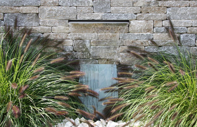 Wasserspiel vor Natursteinmauer in Designgarten