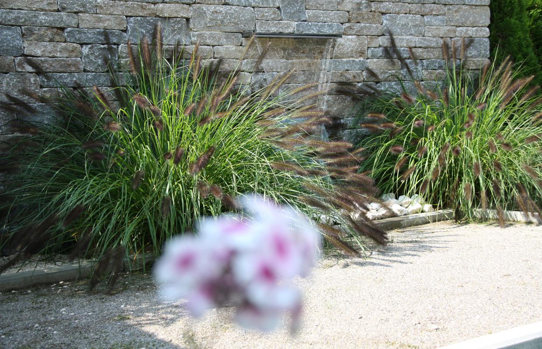 Designgarten Wasserspiel vor Natursteinmauer, Gräserbepflanzung