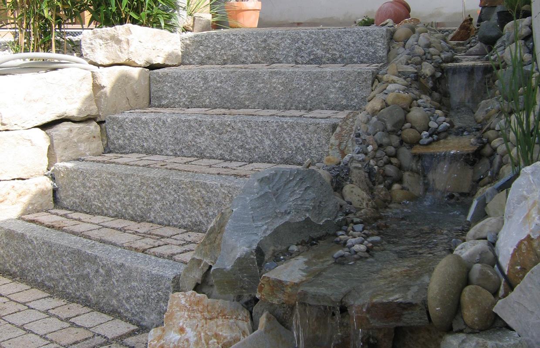 Granittreppe in mediterranem Landgarten und Wasserfall