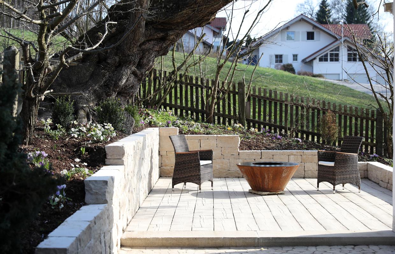 Erhöhter Sitzplatz mit Bodenbelag in Holzdielenoptik und Natrusteinmauer